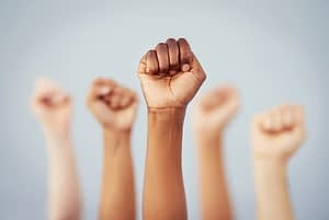 Cropped studio shot of a group of women raising their fists in solidarity against a gray background