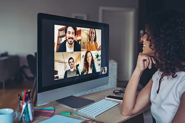 Woman video chatting with four people on computer screen.